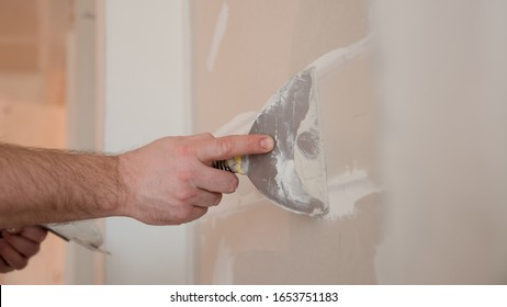 Close Up of a builder hands working with plastering tool.