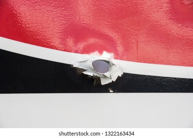 close up of bullet hole in red white and black metal sign