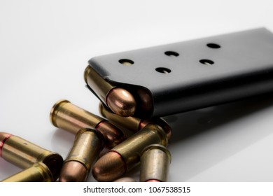 Close up of bullets and magazine clip on white background. Ammunition from a black hand gun magazine macro close up.