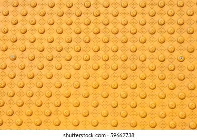 Close up of bumpy yellow patterned walkway.