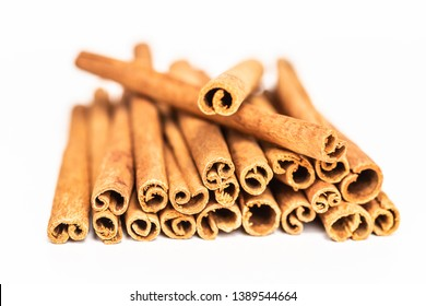 Close up of a bunch of cinnamon sticks on a white backgraound