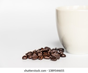 Close up of a bunch of coffee beans by a cropped white coffee cup