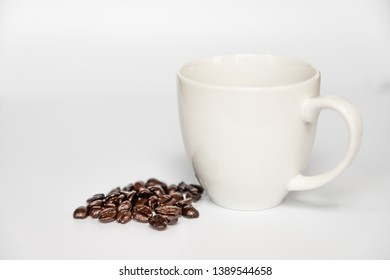 Close up of a bunch of coffee beans by a a white coffee cup