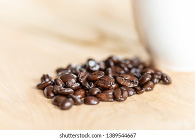 Close up of a bunch of coffee beans by a cropped coffee cup