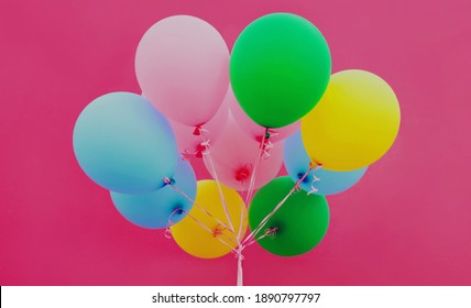 Close up bunch of festive colorful balloons on a pink background