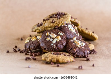 close up of a bunch of freshly baked chocolate chip cookies on brown paper background