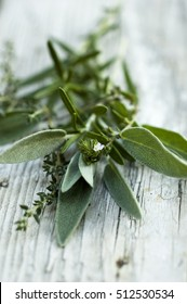 Close up of bunch of mediterranean herbs (sage, rosemary, thyme) on rustic wooden white background