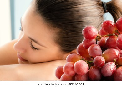 Close up bunch of red grapes with girl in background.Girl having aromatherapy in wine spa.