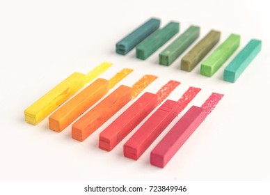Close up of bunch of square colorful pastel chalks and their pigments on white background
