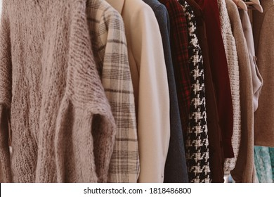 Close up bunch of warm dark colors cozy sweaters and coats with different   patterns hanging in bunch, clearly visible texture. Stylish fall / winter season clothing.