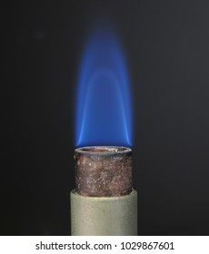 Close up of a Bunsen burner muzzle with low-tipped blue flame used of flammability tests according to UL standard.