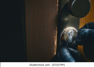 close up of a burglar with gloves picking a lock