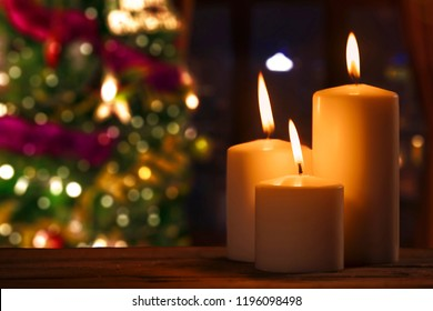 Close up of burned candles on the table with blurred Christmas tree background
