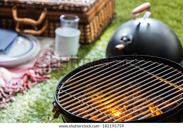 Close up of a burning hot fire in a portable barbecue with an empty grill and a wicker picnic hamper visible on a green lawn behind