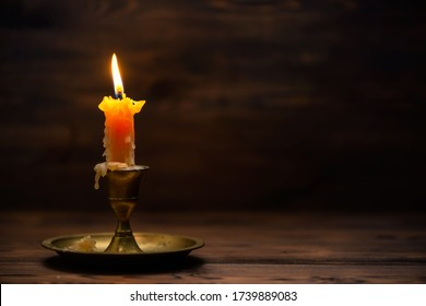close up of burning old candle with vintage brass candlestick on wooden background in minimalist room interior