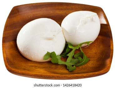 Close up of burrata italian cheese and arugula green leaf at wooden plate. Isolated over white background