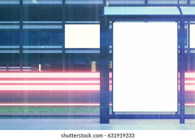 Close up of a bus stop with a blank vertical billboard standing in the night street near a building with glowing windows in the background. 3d rendering, mock up, toned image