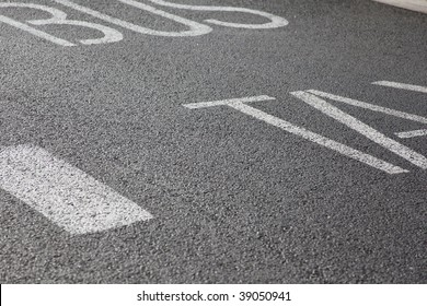 close up of bus and taxi written on asphalt