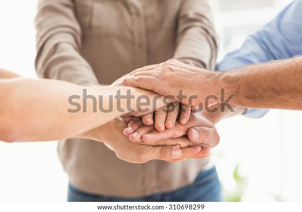 Close up of business colleagues stacking hands together at office
