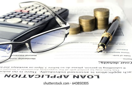 close up of business fountain pen and eyeglasses with calculator and coins stack on loan application document for finance ideas concept