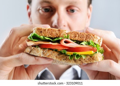 Close up of a business man eating a healthy ham, cheese, tomato sandwich, selective focus on food