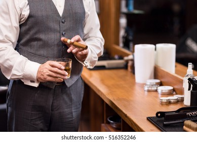 Close up of business man with glass and cigar