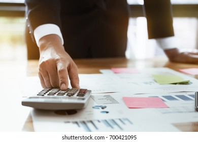 Close up business man hand doing finance and calculate on wooden table about cost at home office. accountant concept.