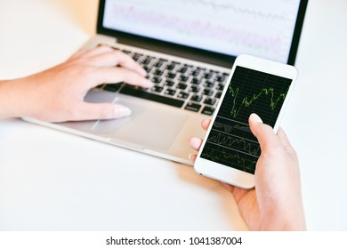 Close up business man hand holding smart phone with candle graph for trade stock market
