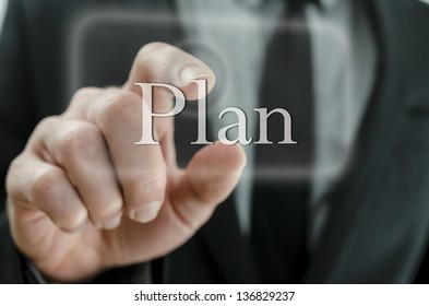 Close up of business man hand pressing Plan button on a touch screen interface. Concept of planning a successful business.