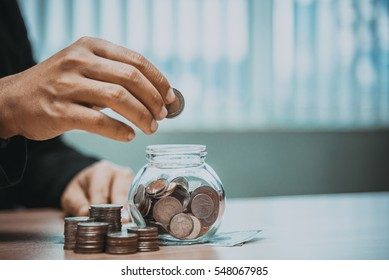 Close up of business man hand putting the coins on the table in his office in finance,investment,saving and banking concept