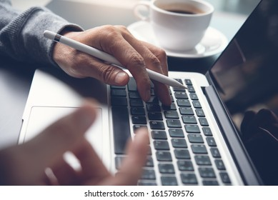 Close up of business man hands with stylus pen typing on laptop computer keyboard browsing internet, Web designer working on laptop, cup of coffee on desk, online working, e business, social network