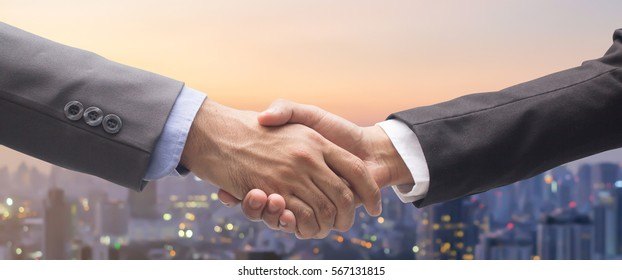 close up business man handshake fro dealing goal isolated on blurred city background,agreement financial commercial, we are hiring concept.