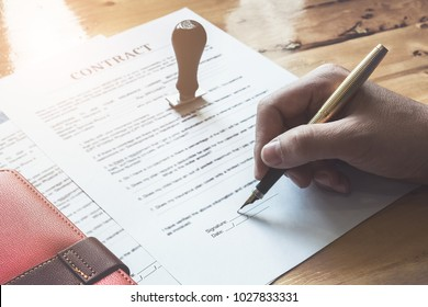 Close up of Business man pointing and signing agreement contract for buying house. Bank manager concept.