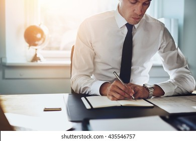 Close up of business man in shirt and tie working in his office writing in a classic note book