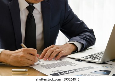 Close up business man signing agreement contract making a deal. (classic business concept to make decision with document and notebook)