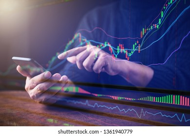close up business man with smartphone and stock chart market black background