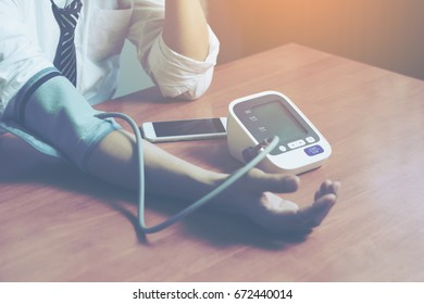 Close up business man tested with Holter monitor hand with sphygmomanometer ,Health care for men with rhythm and blood pressure monitors stove. . Health concept.selective focus