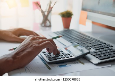 Close up Business man using calculator and laptop for do math finance on wooden desk in office and business working background, tax, accounting, statistics and analytic research concept