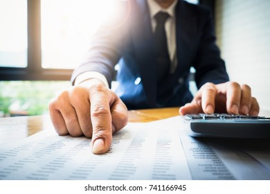 Close up Business man using calculator and laptop computer for calculating with finance paper, tax, accounting, Accountant concept.