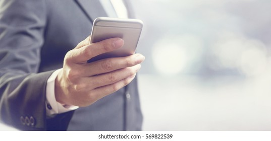 Close up of a business man using mobile smart phone, copy space.
