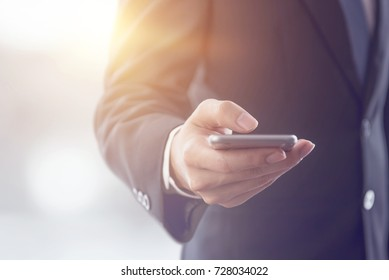 Close up of a business man using mobile smart phone, background for copy.