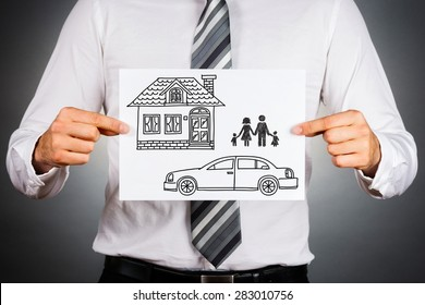 Close up of a business man,holding white card with house,car and family drawing inside.Isolated against grey background.