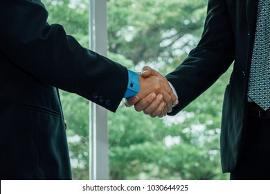 Close up business men shaking hand when deal project done