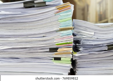 Close up of business papers stack on desk. Pile of unfinished documents on office desk