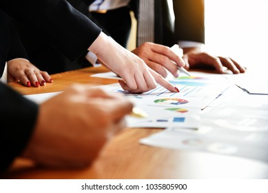 Close up Business People hands are discussing with chart or graph documents at meeting. Teamwork, Brainstorming, Sharing, Solution, Vision, Strategy.