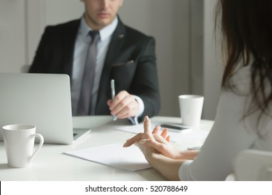 Close up of business people hands hold at an office desk, young man and woman are having a business talk. The woman feels stressed. Business concept photo