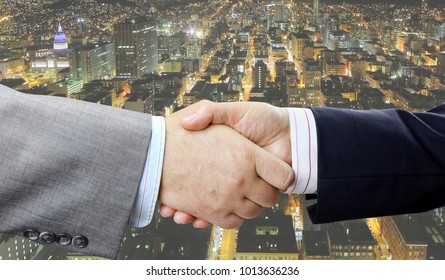Close up of business people handshake on big city at night background