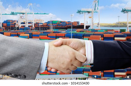 Close up of business people handshake on container terminal with cranes background