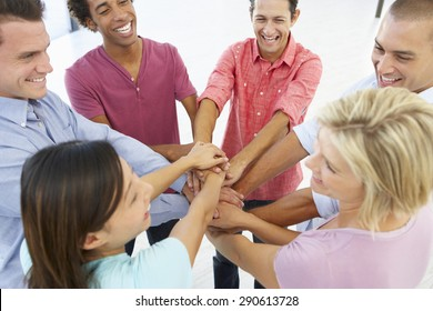 Close Up Of Business People Joining Hands In Team Building Exercise