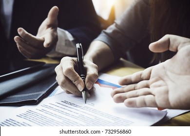 Close up business people reaching out sheet with contract agreement proposing to sign.Full and accurate details, individual who owns the business sign personally,director of the company, solicitor.